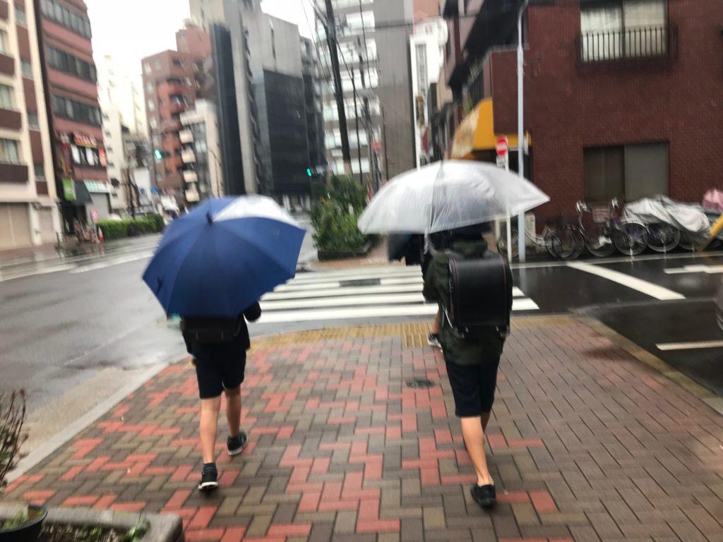 傘をさす小学生の後ろ姿